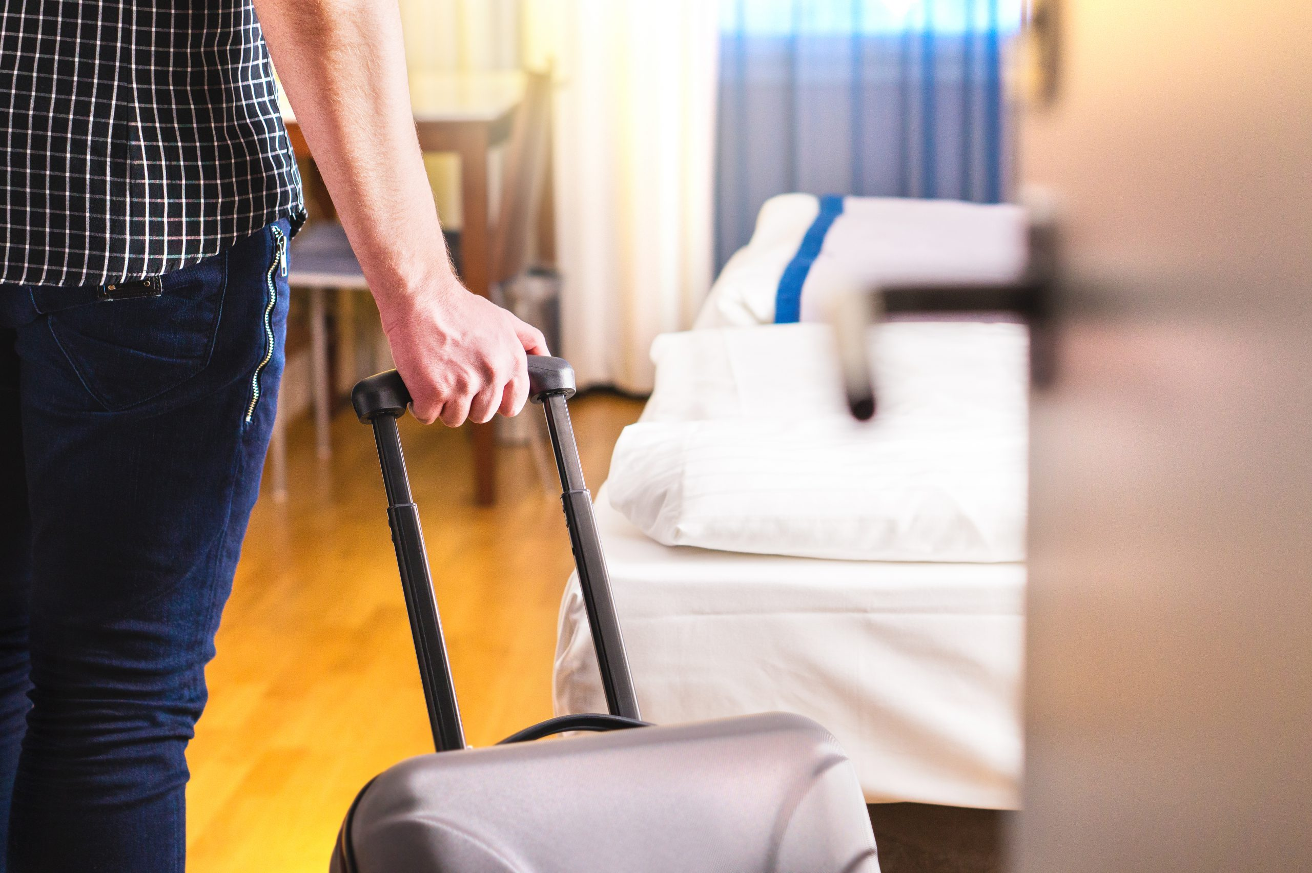 Man pulling suitcase and entering hotel room. Traveler going in to room or walking inside motel with luggage. Emergency lodging apartment rental