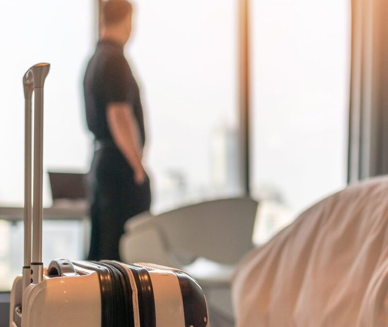 A corporate housing guest standing in a hotel room with a white suitcase